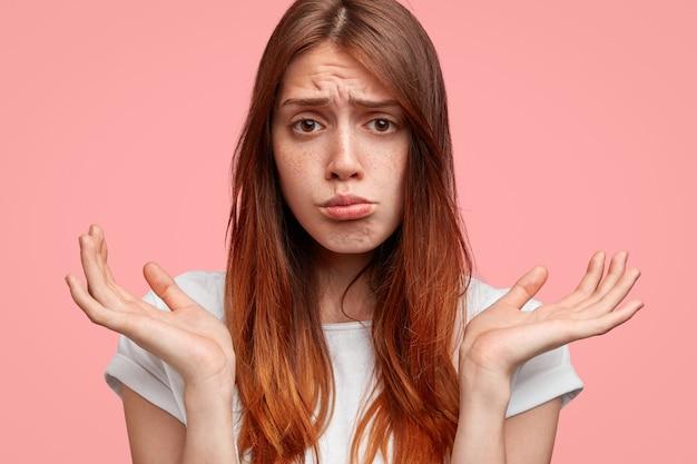 心配して不機嫌なそばかすのある白人女性は下唇を曲げ、肩をすくめて手のひらを上げ、不幸な表情をしています。