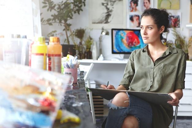 Портрет задумчивой красивой молодой художницы брюнетки в хаки рубашке и рваных джинсах, сидя на стуле у себя дома