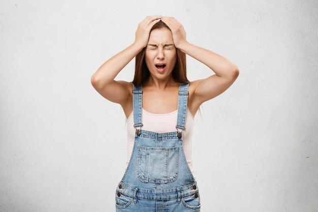 О нет. подчеркнутая женщина-подросток в джинсовом комбинезоне, взявшись за руки на голову, плачет, в панике кричит, понимая, что она забыла сделать то, что сказала ей мать, закрыв глаза от боли, горя и отчаяния
