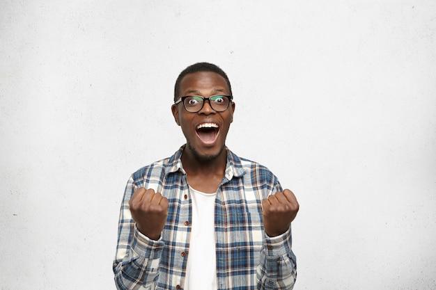 ああ、神様!彼のお気に入りのサッカーチームが試合に勝った後、完全に信じられない思いで見ている、拳を握り締めて興奮して叫んでいるスタイリッシュな服を着たショックを受けて驚かれる若いアフリカ人の肖像画