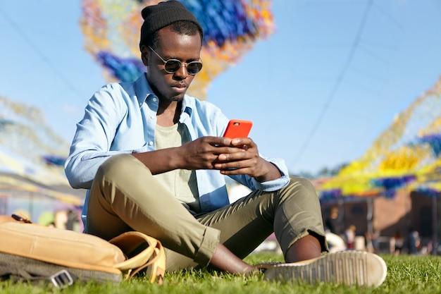 トレンディなシャツとズボンを着た深刻な浅黒い肌の若い男。緑の芝生でリラックスし、赤いスマートフォンを手に持って、インターネットで何かを読んだり、メッセージを入力したりしている。リラックスした黒のおしゃれな男性