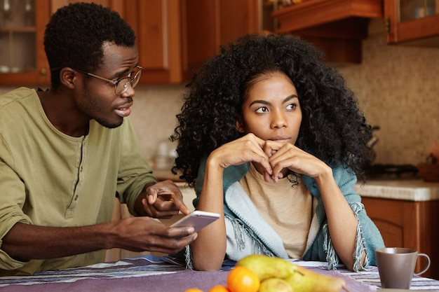 情事のために台所で戦っている若いアフリカ系アメリカ人の家族。携帯電話をかざし、画面に指を向け、見知らぬ女性からの愛のメッセージについて自分を説明しようとするメガネの男