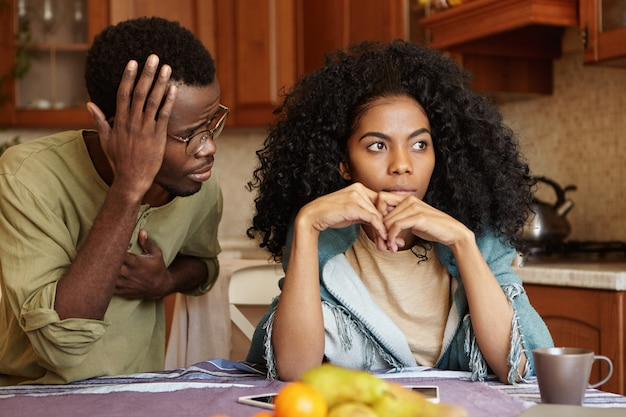 Грустная разочарованная женщина не может простить мужа за неверность, которая сидит рядом с ней с виноватым виноватым взглядом, говоря, что это ошибка. афроамериканец пара сталкивается с проблемами в отношениях