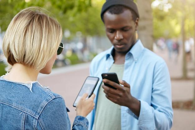 Модный темнокожий мужчина в черной шляпе и рубашке стоит на улице с мобильным телефоном и своей белокурой подругой, пользуется интернетом, обменивается файлами или фотографиями. встреча лучших друзей смешанной расы на улице