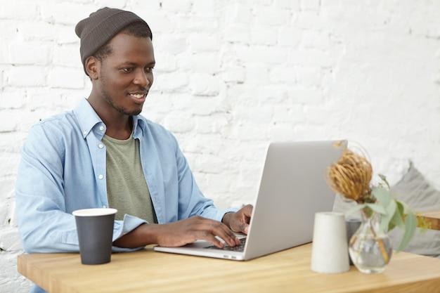 開いたラップトップの前のカフェテリアに座っているハンサムなアフロアメリカンの男。キーボードを使ってインターネットを検索し、コーヒーを飲みます。食堂でクラスの準備をしている浅黒い肌の若い男性学生