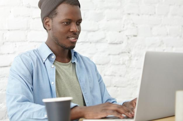 カフェテリアで無料のインターネット接続を使用して、ラップトップで働いて、ソーシャルネットワークをサーフィンし、コーヒーを飲みながらスタイリッシュな服を着た黒人男性の肖像画。カフェで近代的なデバイスを操作するビジネスマン