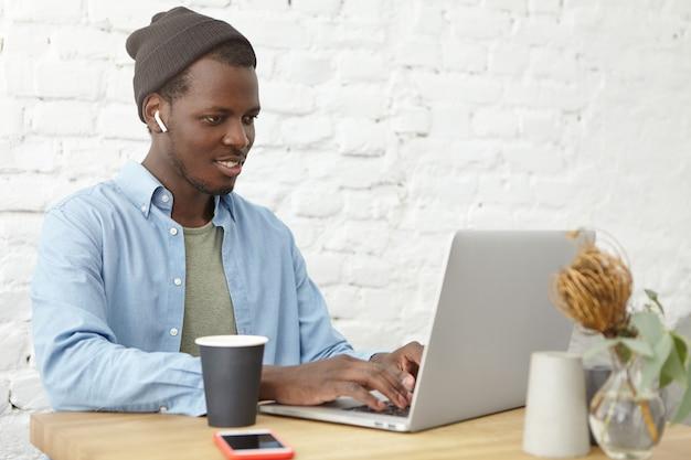 ラップトップでキーボード操作のスタイリッシュな服でハンサムな陽気な若いアフリカ系アメリカ人ヒップスター、カフェで昼食時に無料のインターネット接続を使用して、ワイヤレスイヤホンを使用してお気に入りのトラックを楽しむ