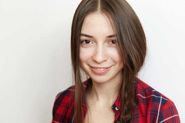 かわいい笑顔と彼女の乱雑な三つ編みを身に着けている幸せな笑顔で健康的なきれいな肌と陽気な若いブルネットの女性の肖像画を間近します。
