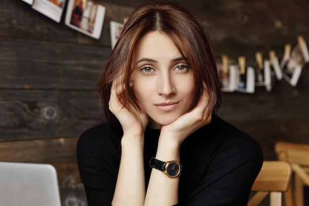Мечтательная красивая молодая кавказская женщина с симпатичным лицом, думая о чем-то, сидя перед портативным компьютером в кафе