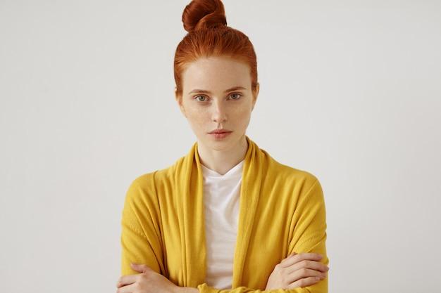 赤い髪のそばかすのある美しい若い女性は、お団子に縛られ、明るい服を着て、手を交差させて、自信を持って探して、孤立しています。美しさと若さの概念