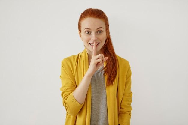 分離された沈黙の兆しを見せながら幸せな表情を持っているポニーテールで結ばれた赤い髪の美しいそばかすのある女性の写真。静けさを言って唇に指を保つ生姜女性