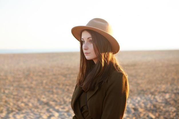 晴れた日に海岸沿いを散歩するスタイリッシュな服を着た魅力的な若いヨーロッパの女性は、夕日を考えて海にやって来ました。砂浜のビーチでリラックスした帽子のきれいな女性
