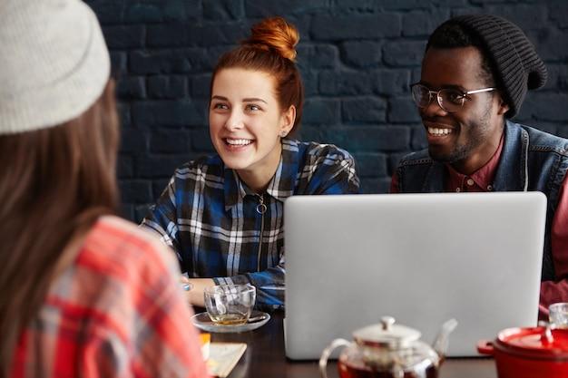 コーヒーショップで現代のガジェットを使用して若い流行に敏感な人種グループ。ビジネス、友情、スタートアップ、チームワーク、コワーキングプロセスの概念。