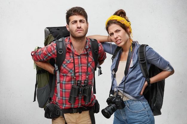 不幸な若い白人の男性と女性の友人は、息をのむような感じ、休息をとり、バックパッキング旅行中に長い登りの後、痛みを伴う表情で見て背中の痛みをマッサージします