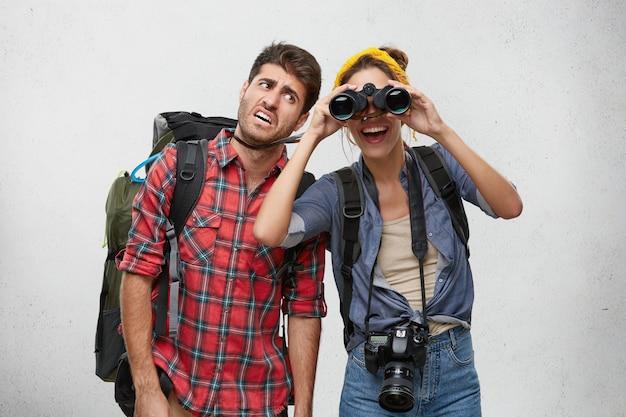一緒にハイキング旅行中に双眼鏡を使ってキャンプする場所を探している写真のカメラで重いバックパックと陽気な興奮した女性を運ぶ疲れたひげを生やした男性観光客の写真。人と冒険