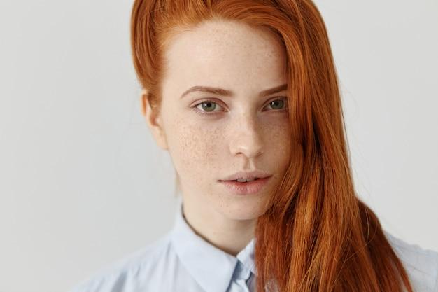 側に緩い赤い髪を着て、正式な水色のシャツに身を包んだ白い壁に立っている彼女のきれいな顔全体にそばかすのある生姜美人