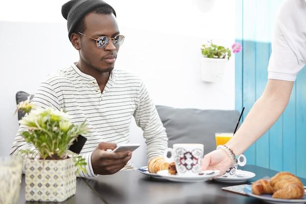 レストランでスタイリッシュな黒肌の男性ゲストテーブルを提供する手に皿が付いた認識できないウェイター。コーヒーショップで提供されている間スマートフォンを使用して流行の服でハンサムな黒人顧客