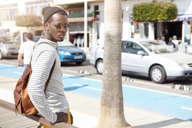 サングラスと流行に敏感な帽子のファッショナブルな魅力的な若いアフリカ系アメリカ人旅行者がバス停に立って、公共交通機関が都市のビーチに行くのを待っています。旅行、冒険、不思議と観光