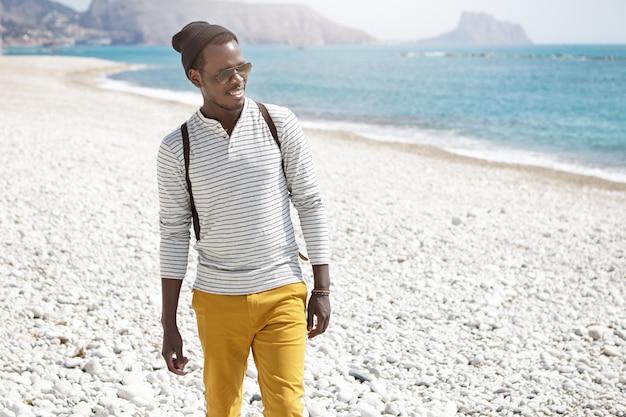 ファッショナブルな若いアフリカ系アメリカ人観光客が午前中に海で遊んでいるイルカを見て幸せそうに笑って都市の小石のビーチに沿って歩く