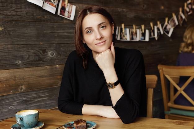 Расслабленная уверенная молодая женщина с темными волосами в черной одежде смотрит с очаровательной улыбкой, положив локоть на деревянный стол с кружкой и десертом, попивая кофе в ресторане