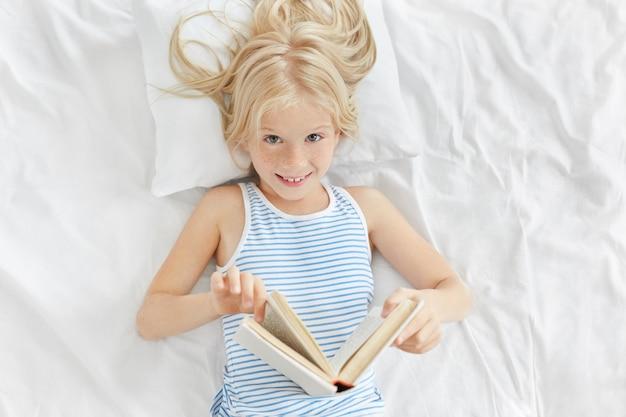 おとぎ話を読んで楽しんでいる彼女の寝室で白い枕の上に横たわるブロンドの髪を持つ陽気な愛らしい少女の屋内撮影。青い目をしたかわいい女性の子供は、昼寝の代わりに読書をしている
