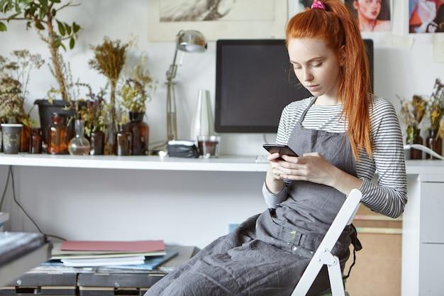 現代の技術、職業、職業のコンセプト。芸術学校の魅力的なジンジャーガール学生の大学のワークショップで椅子に座っているとスマートフォンでメッセージングの友人の率直なショット