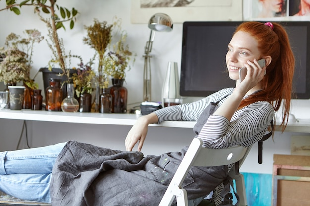 Картина уверенно беззаботной молодой европейской женщины художника расслабляющий на стуле в современной студии, весело улыбаясь, имея хороший телефонный разговор с другом. профессия и технологии