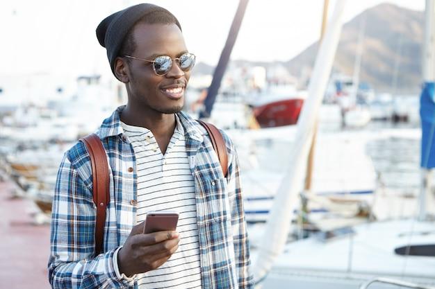 旅行、観光、コミュニケーション、技術、人々の概念。スタイリッシュな帽子を身に着けているバックパックとハンサムな黒人男性と日当たりの良い天気を屋外で楽しんでいるスマートフォンでテキストメッセージの色合い