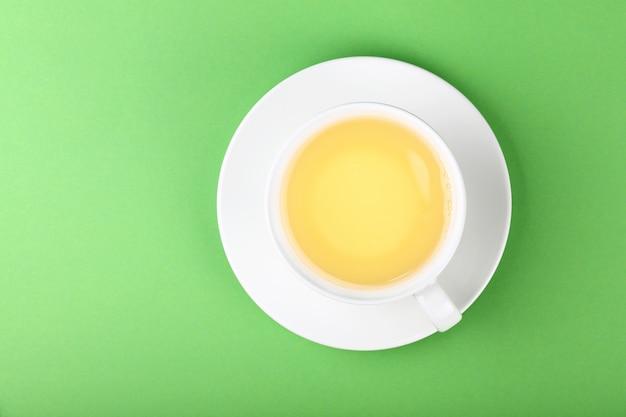 Белая чашка чая на зеленом фоне