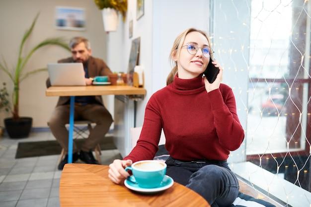 カジュアルな服装でカフェに座っている、一杯のコーヒーを飲んでいるとスマートフォンで呼び出す若い金髪の現代的な女性