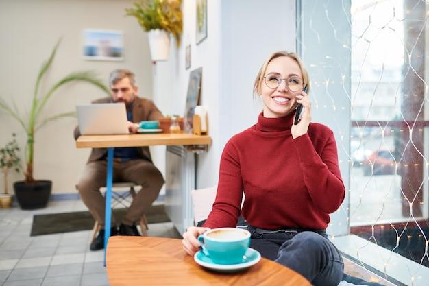 カフェでコーヒーを飲みながら友人や同僚とスマートフォンで話している歯を見せる笑顔で陽気な若い女性