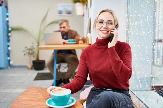 カフェに座って、スマートフォンで呼び出して飲むカジュアルな赤い栗色のプルオーバーで幸せな若い金髪マネージャー