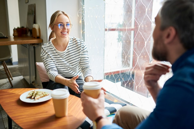 カジュアルな服装でかなり若い陽気な実業家とカフェでの作業質問の議論中にコーヒーを飲んでいる彼女の同僚