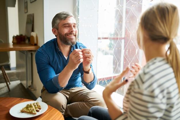 Счастливый молодой влюбчивый человек показывая обручальное кольцо к своей подруге пока делающ ее предложение в кафе