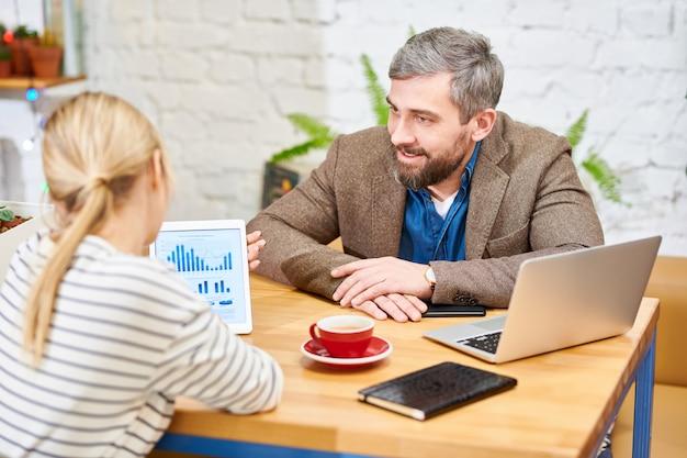 作業会議でタッチパッドのグラフを説明する同僚に聞いて自信を持っての若手実業家