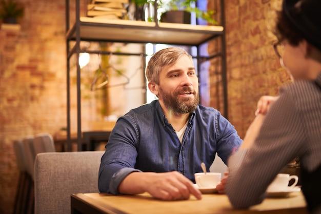 カフェのテーブルに座って、お茶を飲んで、日付に彼のガールフレンドとやり取りするカジュアルウェアのひげを生やした男