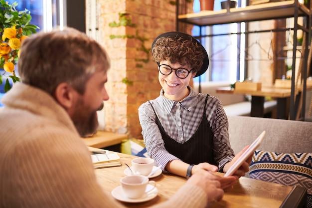 スマートカジュアルで幸せな女と彼女のボーイフレンドがカフェでリラックスしながらタッチパッドで面白いビデオを見て