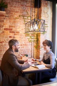 Двое молодых коллег в элегантной повседневной одежде сидят за столом друг перед другом и обсуждают рабочие вопросы