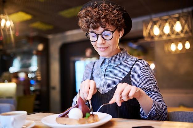 Молодая женщина, принимая кусок груши десерт с ее тарелки, сидя в кафе на обеденный перерыв