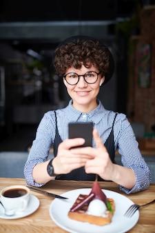 近くのドリンクとデザートのカフェで座っている間彼女のスマートフォンで帽子とスマートカジュアルなスクロールでかわいい女の子