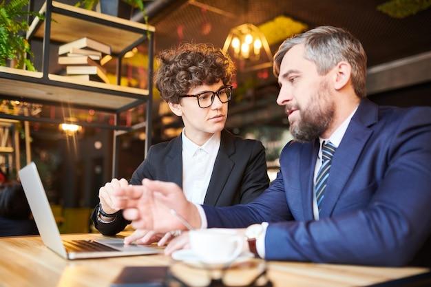 Молодой уверен бизнесмен, объясняя его коллеги данные в ноутбуке во время обсуждения или анализа курса