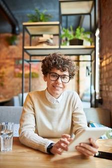 カフェのテーブルでネットワーキングしながらタッチパッドでスマートカジュアルなスクロールで自信を持って若い実業家