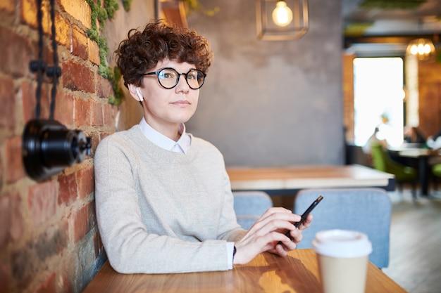 居心地の良いカフェのテーブルでリラックスして音楽を聴きながらスマートフォンでスクロールする暗い巻き毛を持つ物思いにふける女
