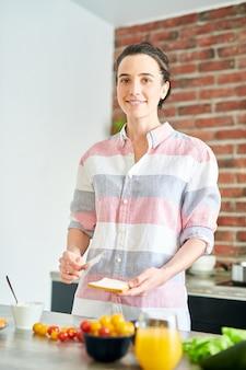 モダンなアパートメントで朝食を調理しながらカメラを見て笑顔の若い女性の肖像画の上半身