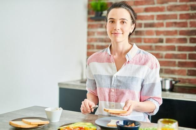 モダンなアパートメント、コピースペースで健康的な朝食を調理しながらカメラを見て笑顔の若い女性の肖像画