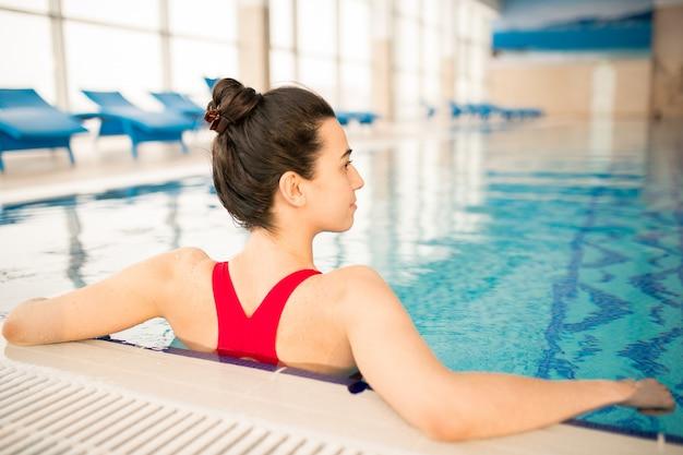 スポーツセンターでのトレーニングの間のスイミングプールで赤い水着立っているブルネットの少女の後姿
