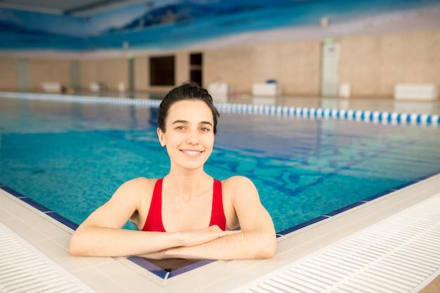 残りの水を楽しみながらカメラの前のプールで水着立っている陽気なかわいい女の子