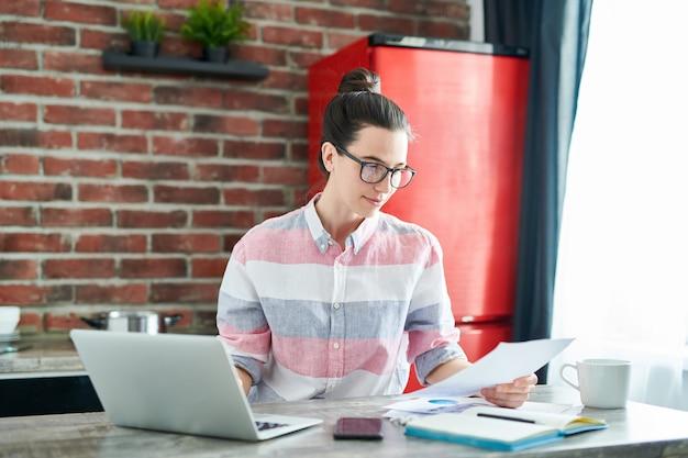 Талия вверх портрет улыбающейся молодой женщины, используя ноутбук и чтение документов во время работы или учебы на дому, копией пространства