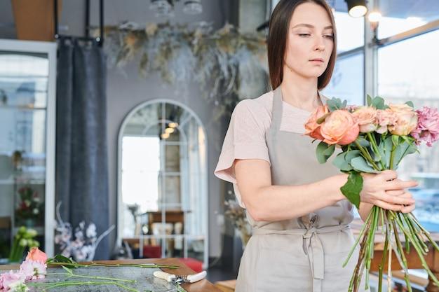 販売のための花を準備している間新鮮なバラの花束をパックしようとする作業服の若いきれいな女性