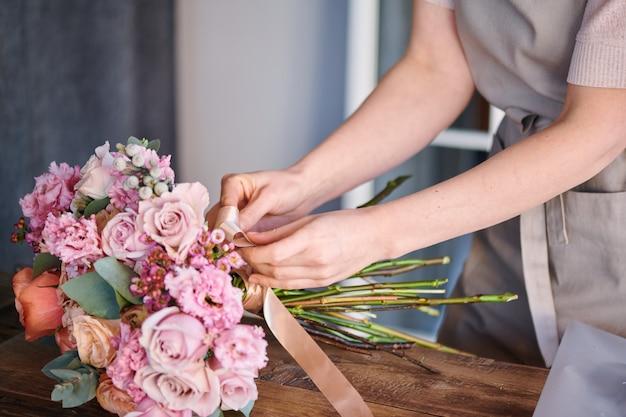 テーブルの上に新鮮なパステル調のバラの束の周りにベージュのシルクリボンを結ぶ花屋やスタジオの所有者